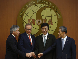 Australia's Defence Minister Smith, Foreign Minister Carr, and South Korea's Foreign Minister Yun and Defence Minister Kim shake hands before their meeting at the Foreign Ministry in Seoul