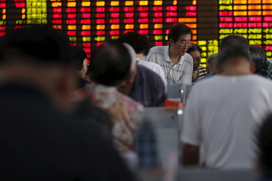 Investors look at computer screens in front of an electronic board showing stock information at a brokerage house in Shanghai