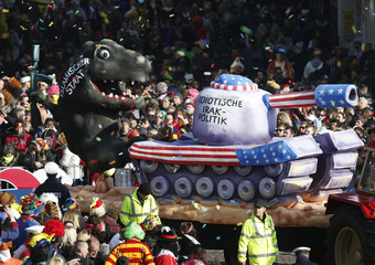 A carnival float with a papier-mache caricature drives past revellers during the traditional Rose Monday carnival parade in Duesseldorf