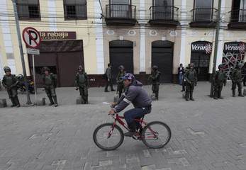 A farmer rides a bicycle in front of riot policemen at the entrance of Facatativa near Bogota