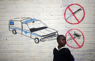 A child walks past a mural at a township school as the school prepares to wish former President Nelson Mandela happy birthday in Atteridgeville near Pretoria