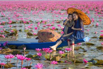 Laos woman in flower lotus lake, Woman wearing traditional Thai people , Red Lotus Sea UdonThani Thailand