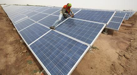 A worker installs photovoltaic solar panels at the Gujarat solar park under construction in Charanka village