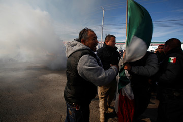 Demonstrators block the way for policemen who are trying to extinguish a car set alight by protesters outside a petrol station, during a protest against a fuel price hike, in Ciudad Juarez, Mexico