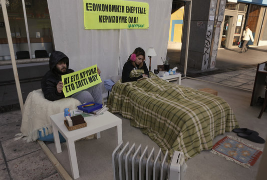 Greenpeace activists sit inside a mock house during a protest to raise awareness on saving energy, outside the Finance Ministry in Athens