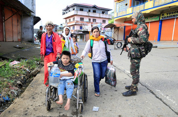 Evacuees walk past a government soldier who is manning a checkpoint at a main street of Marawi city, after government troops' continuous assault with insurgents from the so-called Maute group, who has taken over large parts of the city, in Marawi City