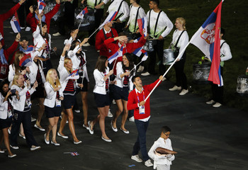Serbia's flag bearer Novak Djokovic holds the national flag as he leads the contingent in the athletes parade during the opening ceremony of the London 2012 Olympic Games at the Olympic Stadium