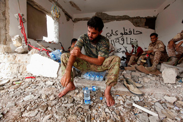 Fighter of Libyan forces allied with the U.N.-backed government washes before praying as he takes rest with his comrades near the front line of fighting with Islamic State militants in Sirte