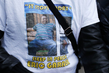 A woman wears a t-shirt with a photo of Eric Garner while people gather at a makeshift memorial, where he died during an arrest in July, at the Staten Island borough of New York