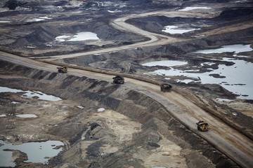 Giant dump trucks haul raw tar sands at the Suncor tar sands mining operations near Fort McMurray.