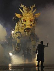 """A guider gestures operators driving a mechanical installation named """"Long Ma"""" during the Long Ma performance in Beijing"""