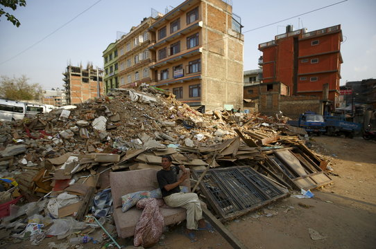 A man sits on the couch near the debris of the collapsed houses, a month after the April 25 earthquake in Kathmandu