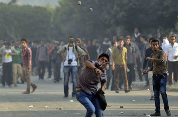 Al-Azhar University student members of Muslim Brotherhood and supporters of Mursi, throw stones, as riot police fired tear gas to stop them marching towards Rabaa al-Adaweya square, in front of Al-Azhar University in Cairo