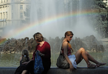 People relax as a rainbow appears in the mist of the Hochstrahlbrunnen fountain in Vienna