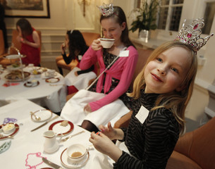Young girls take tea during a 'Princess Prep' class training afternoon to learn how to be a princess in London