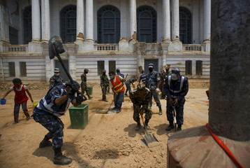 Personnel from the Nepalese army and police, together with locals, work to clear rubble along a street of Bashantapur Durbar Square