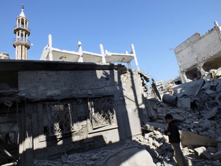 A boy stands near a damaged building after an air strike at a besieged area in Homs