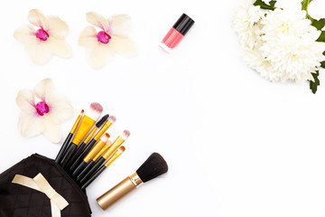 flowers Orchid and chrysanthemum, makeup brushes and nail Polish on white background. Minimal beauty concept. Flat lay