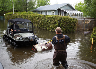 Members of fire department clear debris off flooded streets in Saint-Paul-de-l'ile-aux-Noix Quebec