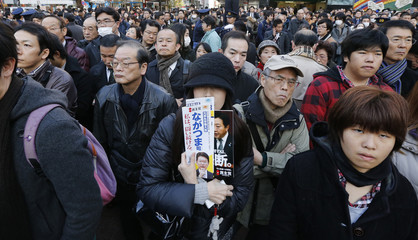 People listen to a speech of Japan's Prime Minister Yoshihiko Noda at a parliamentary election campaign in Tokyo