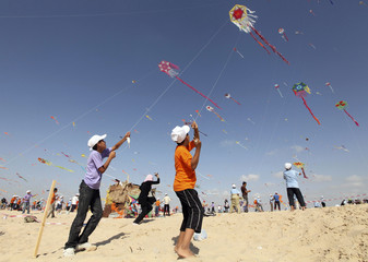 Palestinian children fly kites on the beach of Beit Lahiya