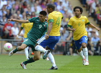 Mexico's Peralta and Brazil's Juan Jesus fight for the ball as Brazil's Marcelo looks on during their men's soccer final gold medal match at Wembley Stadium during the London 2012 Olympic Games