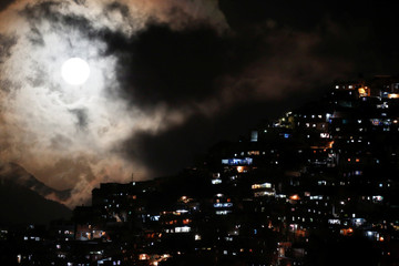 The rising supermoon is seen over the slum of Petare in Caracas