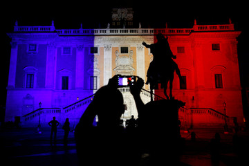 A man take a picture of Rome's city hall as it is lit up in the colors of the French flag, in tribute to the attack victims of Nice, in Rome