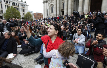 A demonstrator holding her daughter takes a photograph as the Bishop of London speaks to demonstrators camped outside St Paul's Cathedral in London