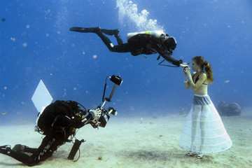 A model opens her mouth to breathe from a scuba tank during an underwater photo shoot in Eilat