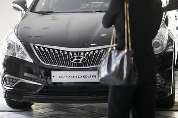 A visitor looks at a Hyundai Motor's Grandeur sedan at its dealership in Seoul