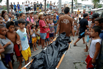 Bodies of Noberto Maderal and fellow pedicab driver George Avancena, killed during a drug-related police operation, are taken away by funeral parlour workers in Manila