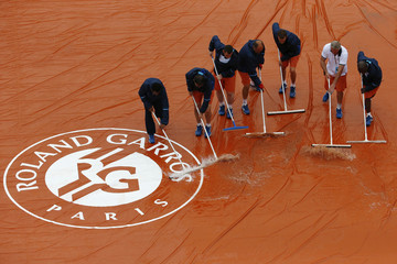 Tennis - French Open - Roland Garros - Court workers sweep away water