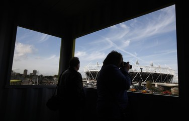 A woman takes a photograph as she looks at the view of the Olympic Stadium and park from a viewing platform in east London