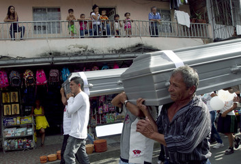 People carry coffins with the bodies of two children killed by armed gangs in Comuna 13 in Medellin