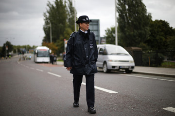 A police officer stands by as Judge Keith Cutler, who is conducting the inquiry into the death of Marc Duggan, and the jury visit the site where Duggan was shot, in Tottenham, north London
