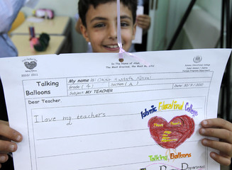 A student of the Islamic Educational College School holds a handwritten Teachers' Day message in Amman