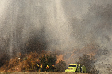 Firefighters stand as water falls from a firefighting aircraft on the Colby Fire in Azusa, California