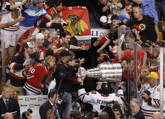Blackhawks' Seabrook carries the Stanley Cup off the ice after they defeated the Bruins in Game 6 of their NHL Stanley Cup Finals hockey series in Boston