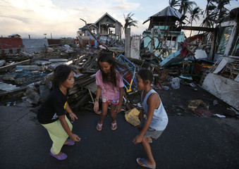 Girls play near typhoon damaged houses in Tacloban city