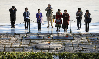 Japanese tourists pay their respects at the Kennedy grave in Washington on the week of the 50th anniversary of his assassination