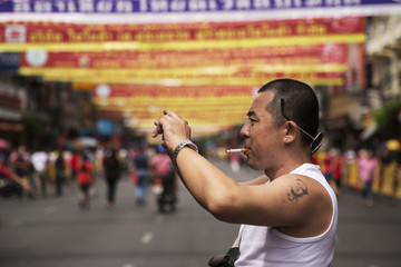 A Chinese tourist with a tattoo of China's late Chairman Mao Zedong takes pictures in Bangkok's Chinatown decorated for the Chinese Lunar New Year