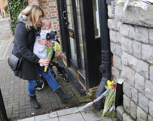 Emma Birch, holds her son Bowie, as she places flowers at the site of the Three Tuns pub in Bromley where David Bowie performed, in south London