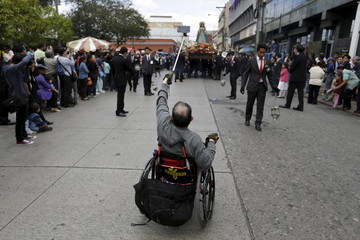 "Handicapped man takes pictures of the religious image of ""Virgen de la Merced"" during a religious procession in Guatemala City"