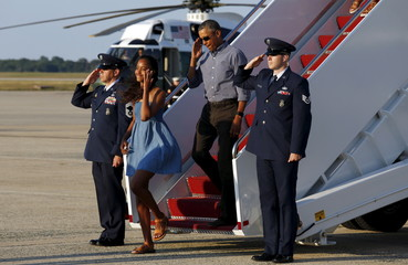 U.S. President Barack Obama salutes as he and his daughter Malia disembark from Air Force One upon the family's return to Washington after a two-week vacation on Martha's Vineyard