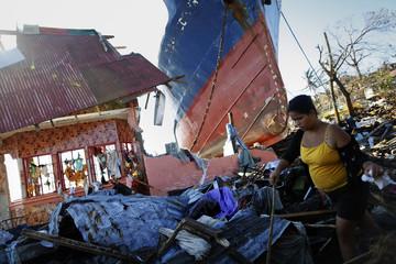 A survivor makes her way through debris of a port devastated by Typhoon Haiyan in Tacloban