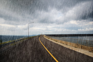 falling rain in road on the ridge of Lam Takong reservoir dam, Thailand