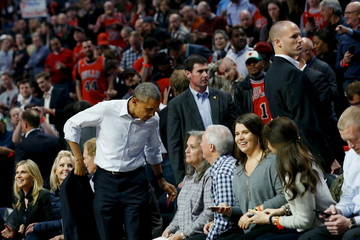Obama takes off his coat as he attends an NBA opening night game between the Cleveland Cavaliers and the Chicago Bulls in Chicago