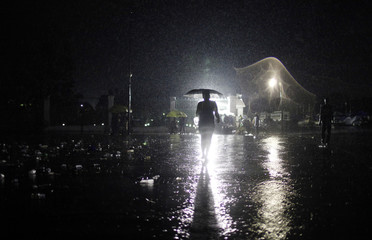 A woman walks under a heavy rain in front of the presidential palace of Port-au-Prince