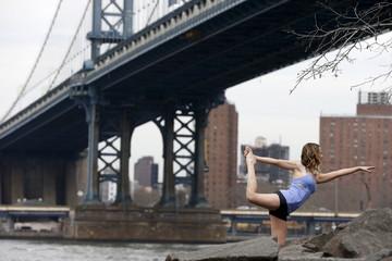 A woman strikes a yoga pose at the Brooklyn Bridge Park in New York